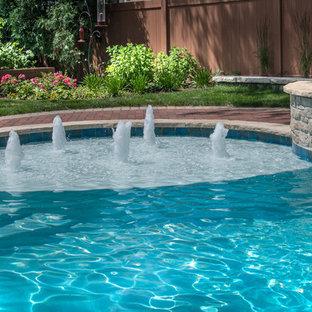 Modelo de piscinas y jacuzzis naturales, de tamaño medio, a medida, en patio trasero, con adoquines de ladrillo