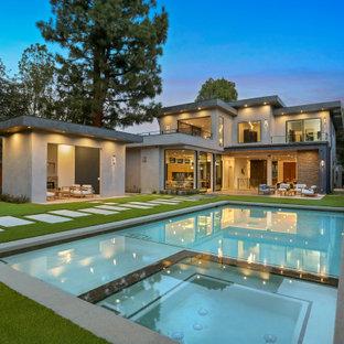 Ejemplo de piscinas y jacuzzis actuales, grandes, rectangulares, en patio trasero, con losas de hormigón