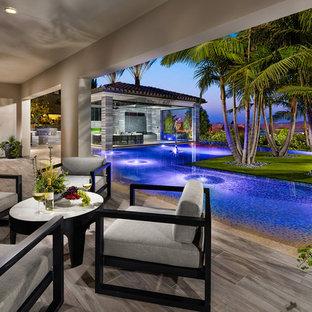 Diseño de casa de la piscina y piscina infinita, tropical, grande, en forma de L, en patio trasero, con suelo de baldosas