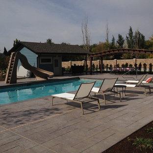 Foto de piscina tradicional, grande, rectangular, en patio trasero, con suelo de hormigón estampado