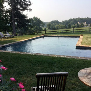 Inspiration for a large country l-shaped pool in Philadelphia with a pool house and natural stone pavers.