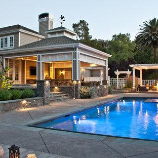 Modelo de piscina campestre, grande, rectangular, en patio trasero, con losas de hormigón