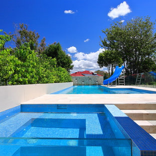Large contemporary backyard l-shaped pool in Sydney with a hot tub.