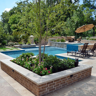 Design ideas for an expansive country backyard custom-shaped natural pool in Houston with a hot tub and tile.