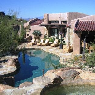 Tuscan stone and custom-shaped pool photo in Phoenix