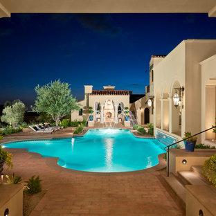 Ejemplo de piscina con fuente mediterránea, grande, a medida, en patio trasero, con adoquines de ladrillo