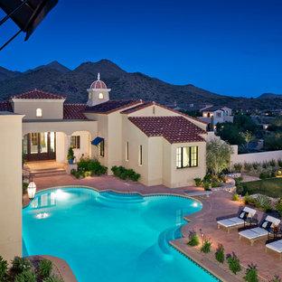 Diseño de piscina con fuente elevada, mediterránea, grande, a medida, en patio trasero, con adoquines de ladrillo