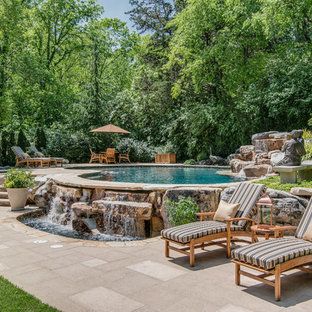 Photo of a mediterranean backyard kidney-shaped pool in Nashville with a water feature.