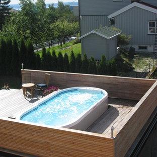 Diseño de piscina elevada, tradicional, grande, a medida, en patio lateral, con entablado