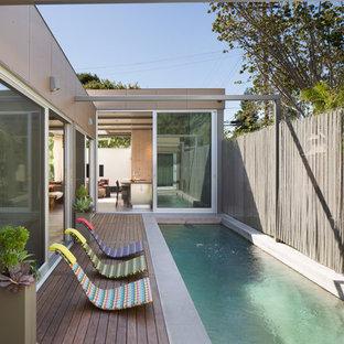 Modelo de piscina infinita, contemporánea, grande, rectangular, en patio trasero, con entablado