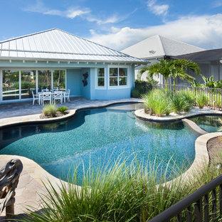 Diseño de piscinas y jacuzzis alargados, rurales, grandes, tipo riñón, en patio trasero, con adoquines de piedra natural