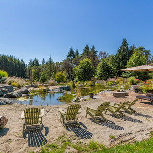 This is an example of an expansive country backyard custom-shaped natural pool in Seattle with a water feature.