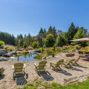 Foto de piscina con fuente natural, rústica, extra grande, a medida, en patio trasero