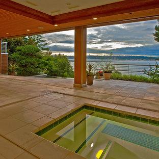 Imagen de piscina clásica renovada, a medida y interior, con adoquines de hormigón
