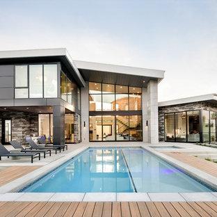 Immagine di una piscina chic rettangolare dietro casa con una vasca idromassaggio e pedane