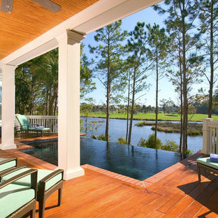 This is an example of a mid-sized beach style backyard rectangular infinity pool in Charleston with decking.