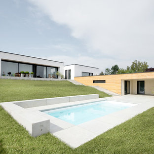 Mittelgroßer Moderner Pool hinter dem Haus in rechteckiger Form mit Betonplatten in Sonstige