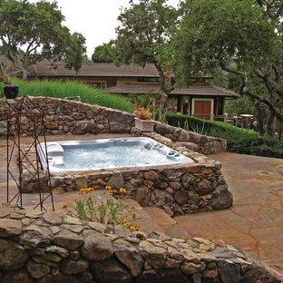 Ejemplo de piscinas y jacuzzis elevados, campestres, pequeños, rectangulares, en patio trasero, con adoquines de piedra natural