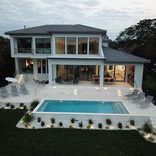 Foto de piscina alargada, actual, grande, rectangular, en patio trasero, con gravilla