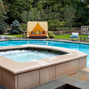 Cette image montre un grand couloir de nage arrière traditionnel sur mesure avec un bain bouillonnant et des pavés en pierre naturelle.