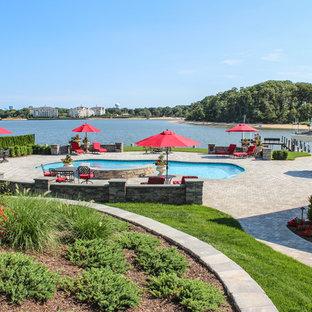 Foto di un'ampia piscina naturale stile shabby personalizzata dietro casa con una vasca idromassaggio e pavimentazioni in cemento
