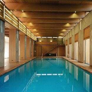 Ejemplo de piscina alargada, urbana, grande, interior y rectangular, con entablado