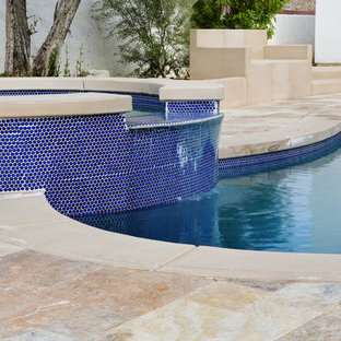 Large mediterranean backyard custom-shaped natural pool in Los Angeles with a hot tub and concrete slab.