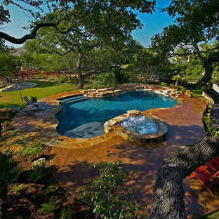 Design ideas for a mid-sized country backyard custom-shaped natural pool in Austin with a water feature and stamped concrete.