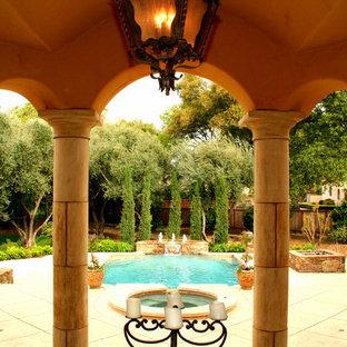 Modelo de piscina con fuente alargada, de estilo americano, de tamaño medio, rectangular, en patio trasero, con losas de hormigón