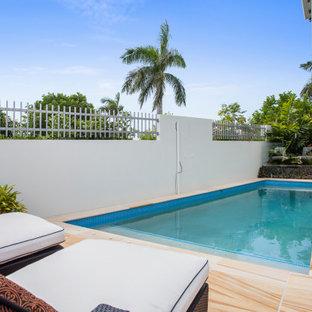 Ejemplo de piscina contemporánea, a medida, en patio lateral, con privacidad y suelo de baldosas