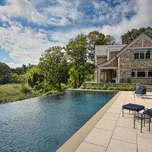 Imagen de casa de la piscina y piscina infinita, clásica renovada, extra grande, rectangular, en patio trasero, con adoquines de hormigón