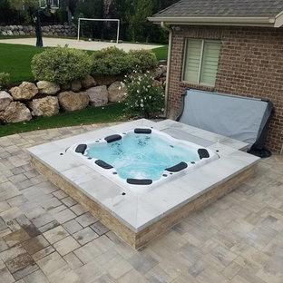 Foto de piscinas y jacuzzis tradicionales, de tamaño medio, en patio trasero, con adoquines de piedra natural