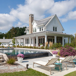 Inspiration for a farmhouse backyard concrete and rectangular infinity pool remodel in Grand Rapids