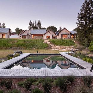 Ejemplo de piscina de estilo de casa de campo, extra grande, rectangular, en patio trasero, con entablado
