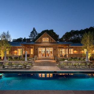 Imagen de piscinas y jacuzzis alargados, de estilo de casa de campo, grandes, rectangulares, en patio trasero, con losas de hormigón