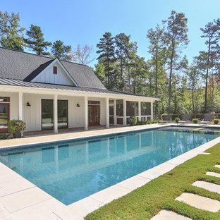 Modelo de casa de la piscina y piscina alargada, de estilo de casa de campo, extra grande, rectangular, en patio trasero, con suelo de hormigón estampado
