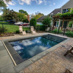 Foto de piscina alargada, clásica, pequeña, rectangular, en patio trasero, con adoquines de ladrillo