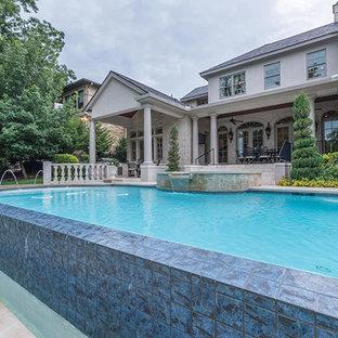 Idee per un'ampia piscina a sfioro infinito vittoriana rotonda dietro casa con una vasca idromassaggio e pavimentazioni in pietra naturale