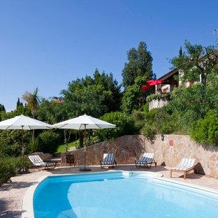 Idées déco pour une grand piscine arrière méditerranéenne sur mesure avec des pavés en pierre naturelle.
