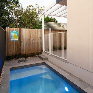Imagen de piscina alargada, costera, pequeña, rectangular, en patio, con privacidad y suelo de baldosas