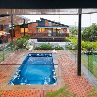 Idee per una grande piscina minimal rettangolare dietro casa con pedane