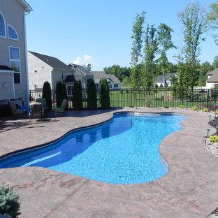 Aménagement d'une grand piscine naturelle et arrière craftsman sur mesure avec un bain bouillonnant et des pavés en pierre naturelle.