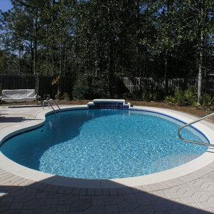 Modelo de piscina natural, tropical, de tamaño medio, tipo riñón, en patio trasero, con adoquines de hormigón
