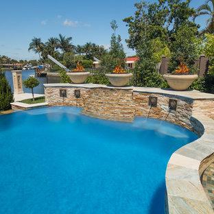 Diseño de piscina natural, contemporánea, extra grande, a medida, en patio trasero, con adoquines de piedra natural