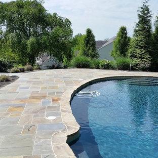 Ejemplo de piscinas y jacuzzis naturales, contemporáneos, grandes, a medida, en patio trasero, con adoquines de piedra natural