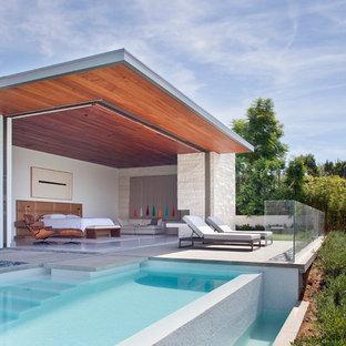 Diseño de casa de la piscina y piscina infinita, contemporánea, rectangular, en patio trasero, con losas de hormigón