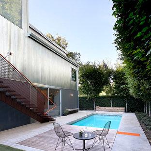 Foto de piscina alargada, urbana, de tamaño medio, rectangular, en patio trasero, con losas de hormigón