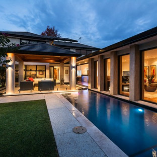 Photo of a small contemporary side yard rectangular lap pool in Perth with tile.
