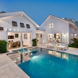Maritimer Pool hinter dem Haus in rechteckiger Form mit Natursteinplatten in Miami