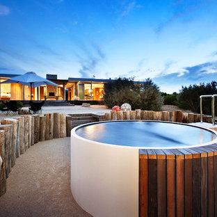 Foto di una piccola piscina fuori terra minimal rotonda dietro casa con una vasca idromassaggio